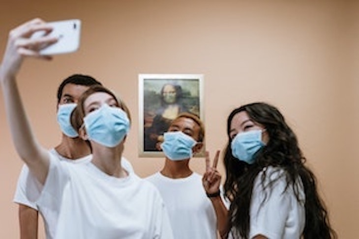 Group shot of people wearing COVID masks taking a selfie